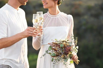 Happy newlyweds with beautiful field bouquet and glasses of champagne outdoors, closeup