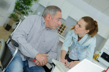 Young lady and disabled man talking by laptop