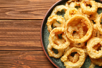 Homemade crunchy fried onion rings on wooden table, top view. Space for text