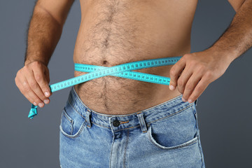 Overweight man with measuring tape on gray background, closeup