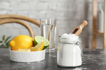 Jar with baking soda and lemons on table indoors