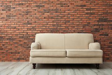 Room interior with comfortable sofa near brick wall