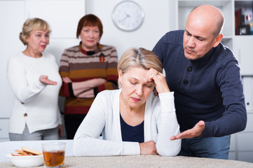 Mature female is sitting upset and man is apologizing