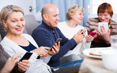 Mature women and man are resting with smartphones