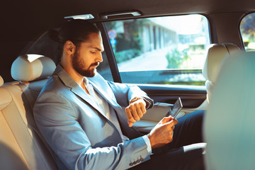 Businessman looking at the watch on the back of the limousine