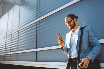 Young modern businessman using a smartphone outdoors