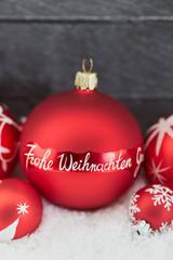 Frohe Weihnachten als Text auf Christbaumkugel