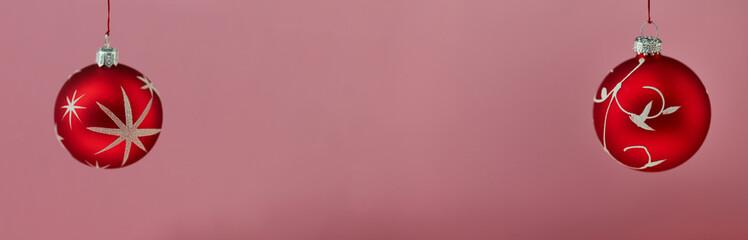 Rote Weihnachtskugel vor einem rosa Hintergrund