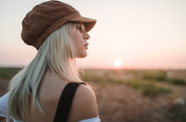 Young blonde woman with beret thinking with tired expression in the middle of desert sunset background