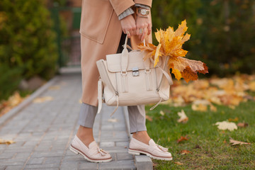 Stylish beautiful woman walking on the street wearing a beige coat, a bag, a warm sweater, a fashionable outfit, an autumn trend, accessories Wall mural
