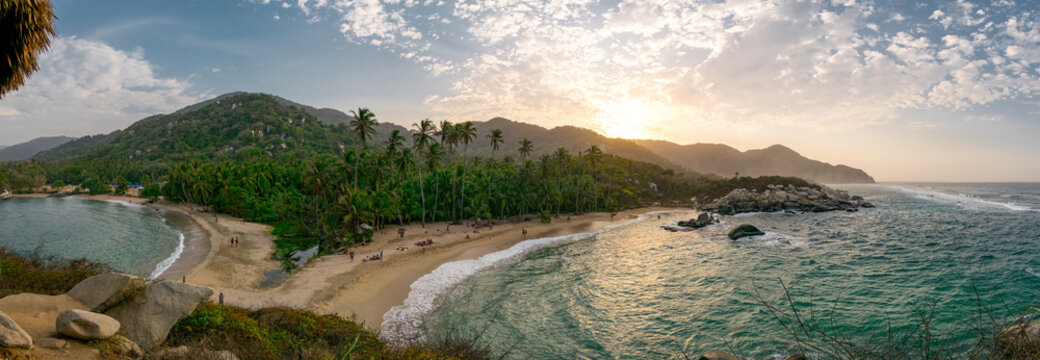Beautiful Caribbean beach with palm trees and sunset in Tayrona National Park close to Santa Marta in Northern Colombia