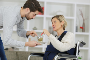 caregiver giving cup of tea to disabled woman in wheelchair