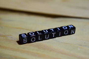 Solution message written on wooden blocks. education and motivation concepts. Cross processed image on Wooden Background
