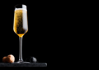 Elegant glass of yellow champagne with cork and wire cage on black marble board on black background. Space for text