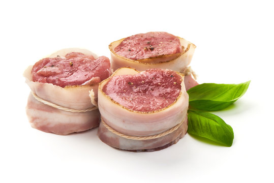 Raw Pork medallions wrapped in bacon with basil leaves, isolated on white background.