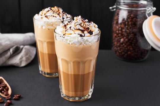 Iced caramel latte coffee in a tall glass with chocolate syrup and whipped cream. Dark background with copy space.