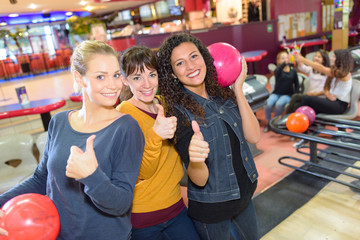 Women with thumbs up in bowling hall
