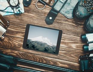 Mount Elbrus on screen of tablet among travel equipment.