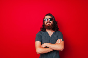 Portrait of bearded man wearing sunglasses over red background
