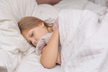 little girl lying in bed with abdominal pain, painful disease, feeling unwell, ache concept