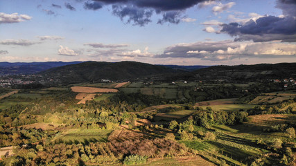 Aerial view of beautiful autumn sunset with a lot of clouds. Amazing colors and shadows of the clouds on the land. Landscape of village in Sumadija near the Kragujevac.