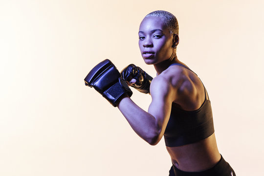 Young woman boxing, against a blank studio background