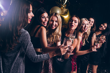 Pure celebration. Beautiful young women in evening gown holding champagne glasses and looking at camera with smile while celebrating in nightclub