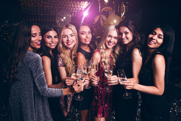 Lets drink for success! Beautiful young women in evening gown holding champagne glasses and looking at camera with smile while celebrating in nightclub