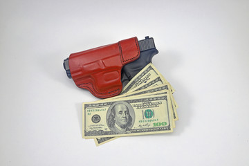Gun in holster with cash