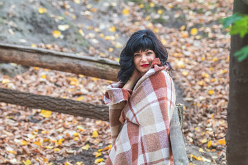Cute happy beautiful sexy brunette female girl resting sitting in autumn garden on the steps, wrapped in a woolen plaid blanket.