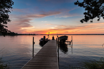 Fototapeta Beautiful lake sunrise sunset with a young woman sitting on the end of a dock, with a boats. on either side. Colorful tranquil vacation scene with concepts of peacefulness and beauty obraz