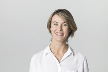 Smiling positive female with attractive look, wearing white elegant shirt posing against white wall