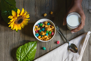 Close up of cereal with glass of milk and sunflower on table