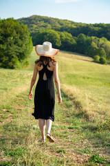 une femme de dos dans la campagne , en robe noire et un grand chapeau
