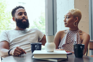 Young couple talking with each other in cafe