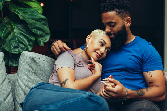 Young couple embracing each other while sitting on sofa