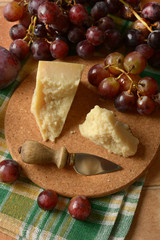 parmesan cheese on the table with bunch of grapes