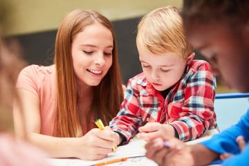 Kindergärtnerin hilft Kindern beim Zeichnen