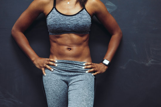 Mid section of a woman standing in gym