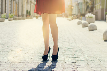 pretty lady walking in the city. Close up photo of long  legs wearing high-heels, city on background sun beam light sunbeam rays sunshine shine sunburst burst  flash shiny flare effect glare sparkle
