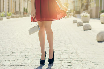 Lady having a date with her boyfriend. Cropped photo of woman's legs in high-heels in the street. Sun beam light sunbeam rays sunshine shine sunburst burst  flash shiny flare effect glare sparkle