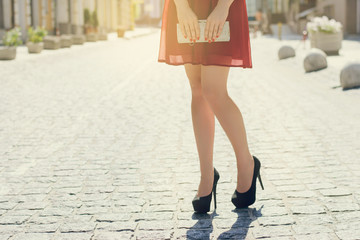 Close up photo of woman's long legs view of city red dress black high-heels and holding bag in hands. Sun beam light sunbeam rays sunshine shine sunburst burst  flash shiny flare effect glare sparkle