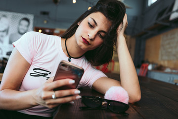 Young woman using smartphone in coffee shop
