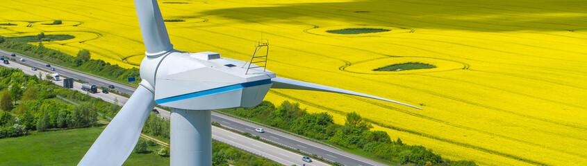 Windkraftanlage an Autobahn und gelbem Rapsfeld Panorama ökostrom