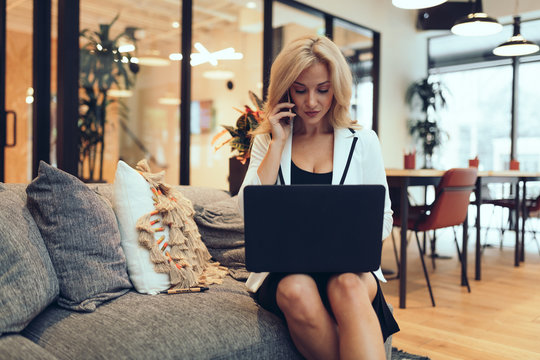Young businesswoman working on laptop while talking on smartphone