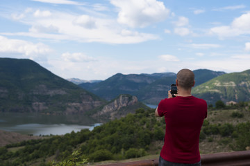 Young Man Taking Pictures With Mobile Smartphone Of Mountain and Landscape