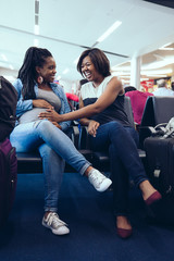Smiling women sitting together at airport waiting room
