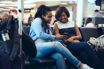 Women using smartphone while sitting at airport waiting room
