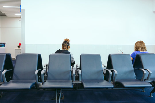 Rear view of woman sitting at airport waiting room