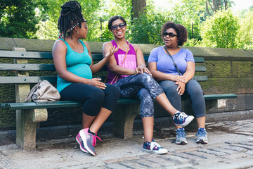 Pregnant woman sitting on bench with friends